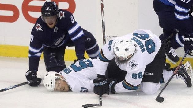 Ke zraněnému Radimu Šimkovi (uprostřed) ze souboje s Andrewem Coppem z Winnipegu (vlevo) se sklání spoluhráč ze San Jose Brent Burns.