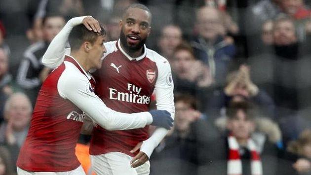 Alexis Sanchez a Alexandre Lacazette z Arsenalu oslavují gól proti Tottenhamu v Premier League.