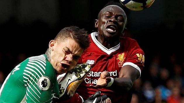 Gólman Manchesteru City Ederson Moraes inkasuje úder kopačkou do hlavy od Maného z Liverpoolu.