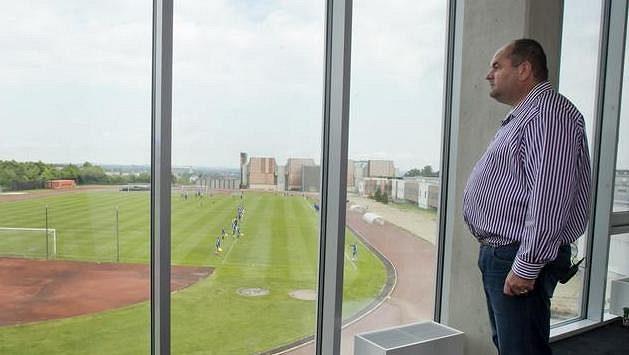 Předseda FAČR Miroslav Pelta dívá z kanceláře na stadión Přátelství s fotbalovým hřištěm a atletickou dráhou.