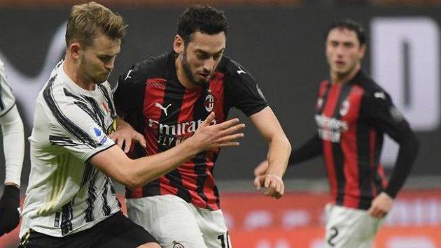 Matthijs de Ligt (vlevo) z Juventusu v souboji o míč s Hakanem Calhanogluem z AC Milán.