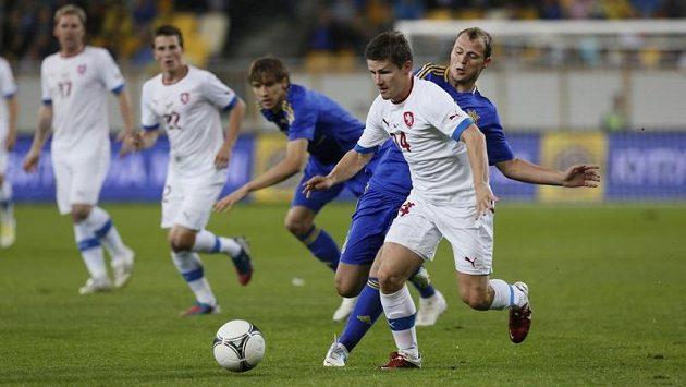 Václav Pilař (v bílém) se snaží udržet míč před dotírajícím soupeřem z Ukrajiny. Za pár minut skončil na nostíkách.