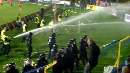 Fotbaloví fanoušci Sparty utíkají před sprškou vody.