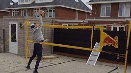 Plážový volejbalista trénuje na zahradě, soupeřem mu je deska opřená o plot